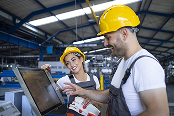Factory worker explaining trainee how to operate industrial machine using new software on touch screen computer.
