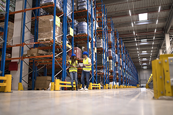 Warehouse workers discussing about logistics and distribution packages to the market.